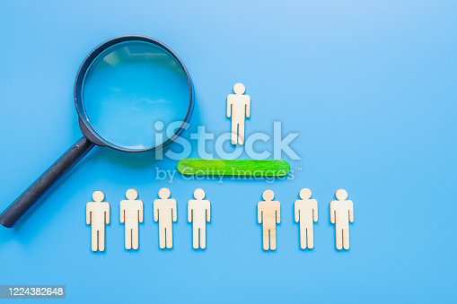 898212112 istock photo Selected wooden figure on blue background. The concept of finding an employee in business. HR manager search employee. Group leader. 1224382648