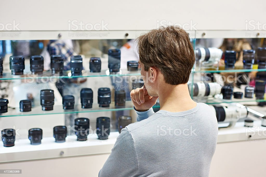 Selecting camera lens in store stock photo