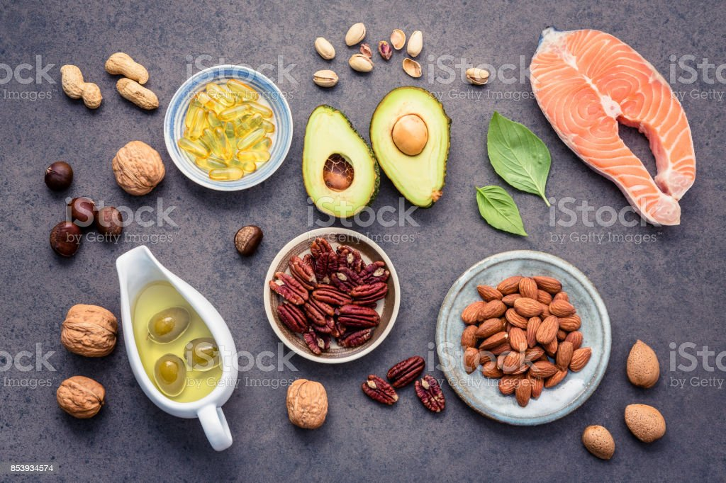 Selection food sources of omega 3 and unsaturated fats. Superfood high vitamin e and dietary fiber for healthy food. Almond ,pecan,hazelnuts,walnuts,olive oil,fish oil and salmon on stone background. stock photo