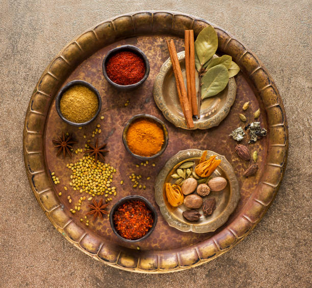 Selection Indian Spices and seasonings in bowls on a metal tray, top view Selection Indian Spices and seasonings in bowls on a metal tray, top view garam masala stock pictures, royalty-free photos & images