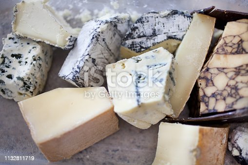 Stone cutting board piled with 10 large chunks of artisan cheese