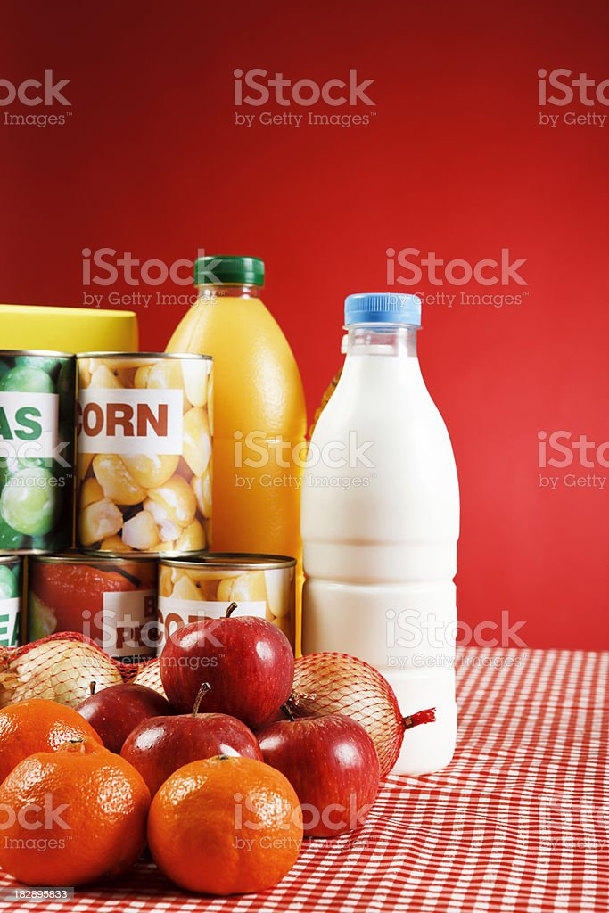 Selection of basic foods on gingham against red background stock photo