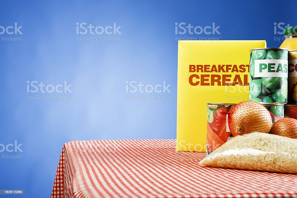 Selection of basic foods on red tablecloth against blue background stock photo