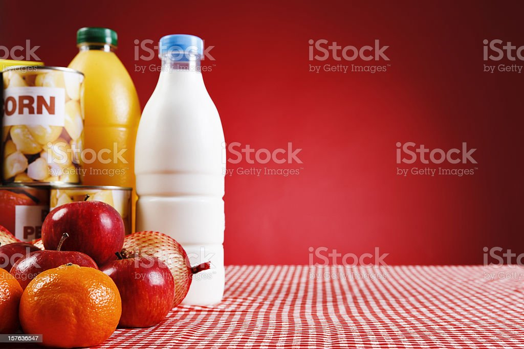 Selection of basic fresh and packaged foods against red stock photo