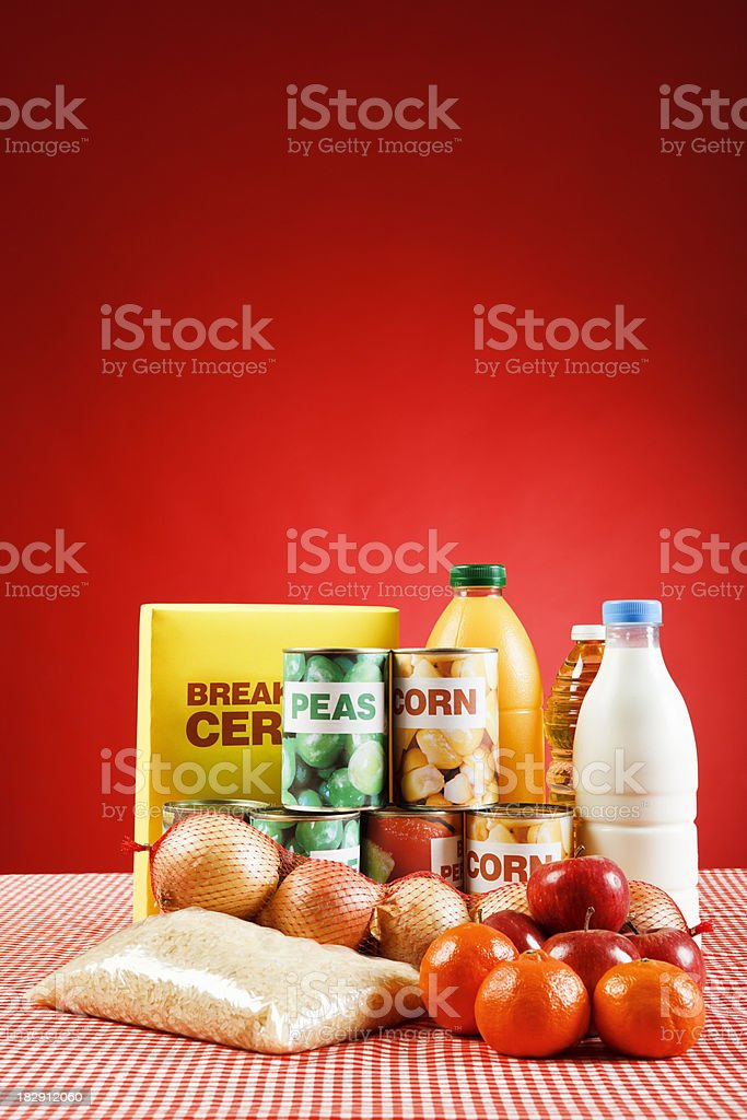 Selection of basic fresh and packaged foods, on red royalty-free stock photo
