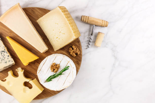 Selection of cheeses with corkscrew, cork, and copyspace stock photo