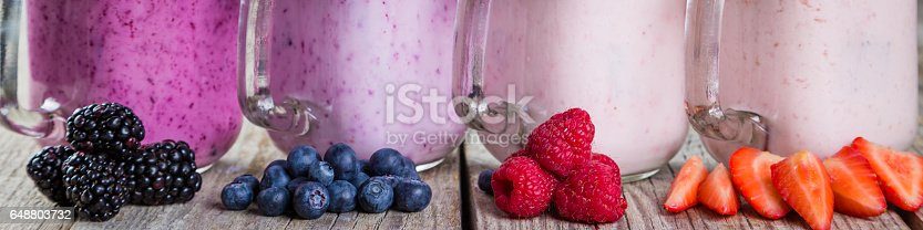 648804276 istock photo Selection of colorful detox berry drinks on wood background 648803732