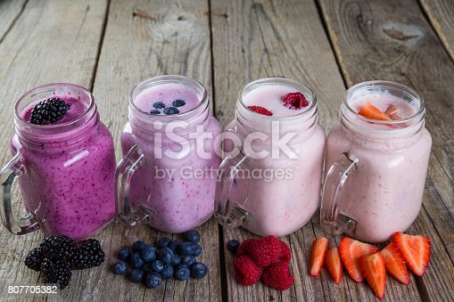 648804276 istock photo Selection of colorful detox berry drinks on wood background 807705382