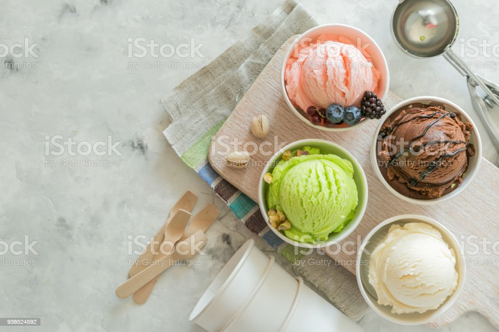 Selection of colorful ice cream scoops in paper cones stock photo