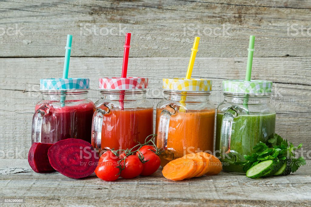 Selection of colorful vegetable juices in glass jars stock photo