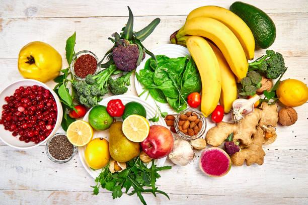 Auswahl an Lebensmitteln reich an Antioxidantien und Vitaminen und Mineralquellen, vegane Nahrung auf weißem Holzhintergrund. Gesundes ausgewogenes Diätkonzept, Zutaten zum Kochen. Ansicht von oben, flach liegen, Kopierraum. – Foto