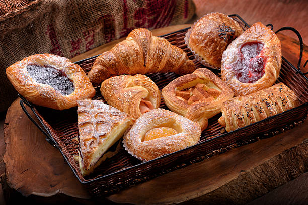 Selection of French & Danish pastries on a Wicker basket Selection of French & Danish pastries on a Wicker basket  pastry dough stock pictures, royalty-free photos & images