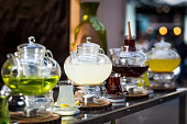 Close up color image depicting a variety of exotic and fruit teas for sale at an outdoor food and drink market. The tea - including lemon and ginger, and mint tea - is being infused inside clear glass teapots on the bar counter. The serving staff are defocused in the background.