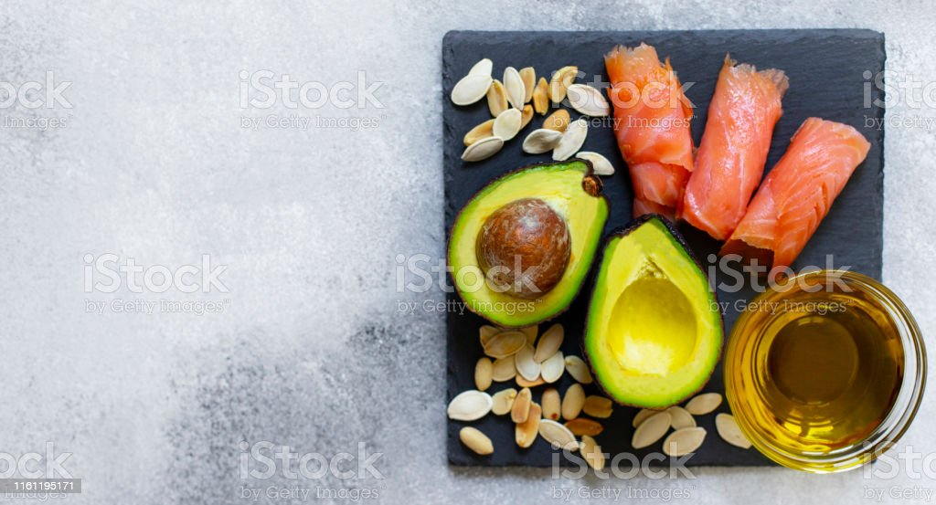 Selection of healthy fat sources, avocado, salmon, nuts, olive oil on...