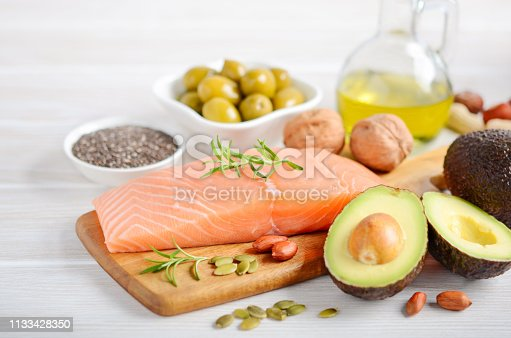 Selection of healthy unsaturated fats, omega 3 - fish, avocado, olives, nuts and seeds, selective focus.