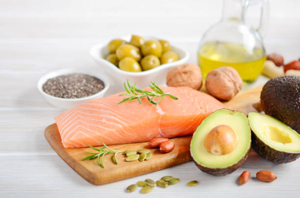 Selection of healthy unsaturated fats, omega 3 - fish, avocado, olives, nuts and seeds. Selection of healthy unsaturated fats, omega 3 - fish, avocado, olives, nuts and seeds, selective focus. ketogenic diet stock pictures, royalty-free photos & images