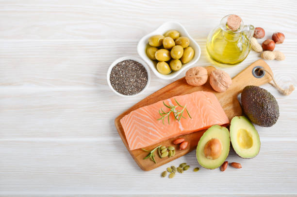Selection of healthy unsaturated fats, omega 3 - fish, avocado, olives, nuts and seeds. stock photo