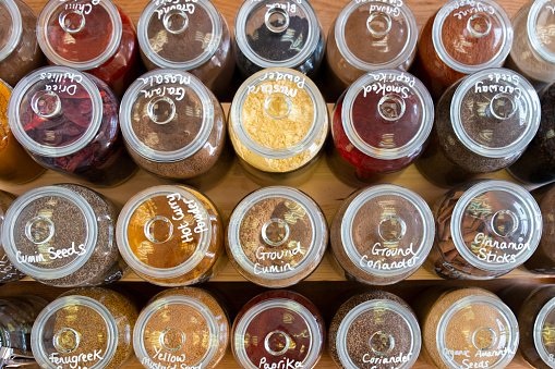 A selection of herbs and spices in clear glass jars on a shelf in a plastic free store.