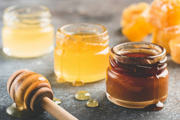 selection of honey in small honey jars - miele foto e immagini stock