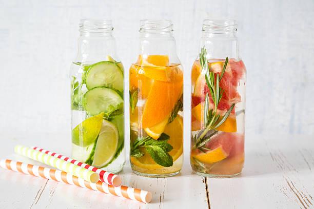 sélection d'eau infusée dans les bouteilles en verre, fond de bois rustique - infusion pamplemousse photos et images de collection