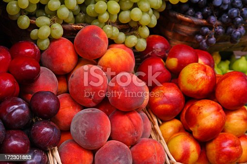 Nectarines, plums, peaches and green and red grapes at an Italian market stall. Fresh, tasty and very healthy fruits