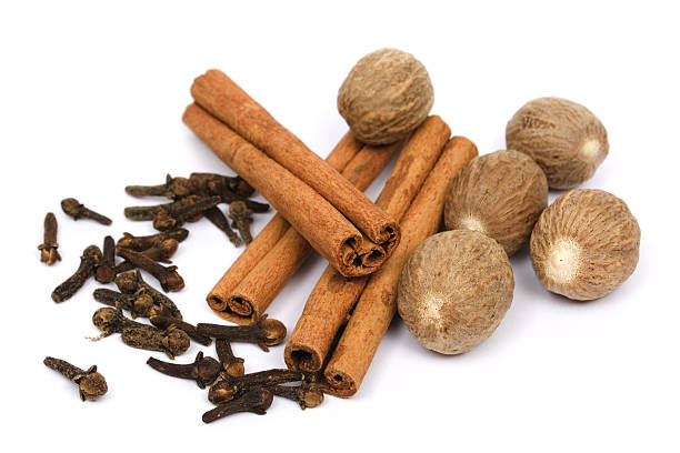 Selection of nutmeg, cinnamon sticks and cloves Nutmeg, cinnamon sticks and cloves isolated on white nutmeg stock pictures, royalty-free photos & images