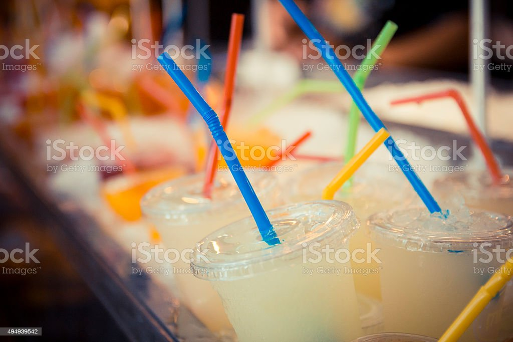 Selection of plastic cups with grapefruit juice and colored straws stock photo