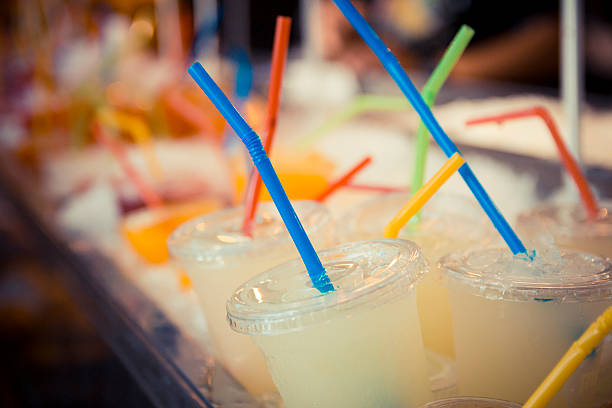 Selection of plastic cups with grapefruit juice and colored straws Selection of plastic cups with grapefruit juice and colored straws, in red, yellow, blue and green. Close up and Focus Selective drinking straw stock pictures, royalty-free photos & images
