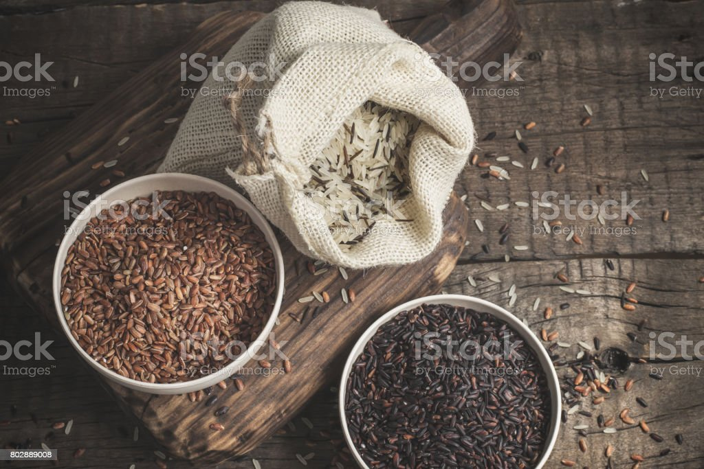 Selection of red, black and mixed rice on an old wooden background.Top view with copy space stock photo