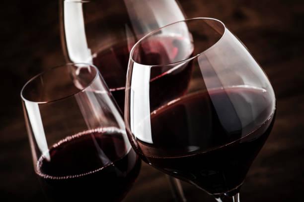 selección de vino tinto en cata de vinos. vinos tintos secos, semisecos y dulces en copas de vino especiales sobre fondo de mesa de madera vieja. copiar espacio - vino tinto fotografías e imágenes de stock