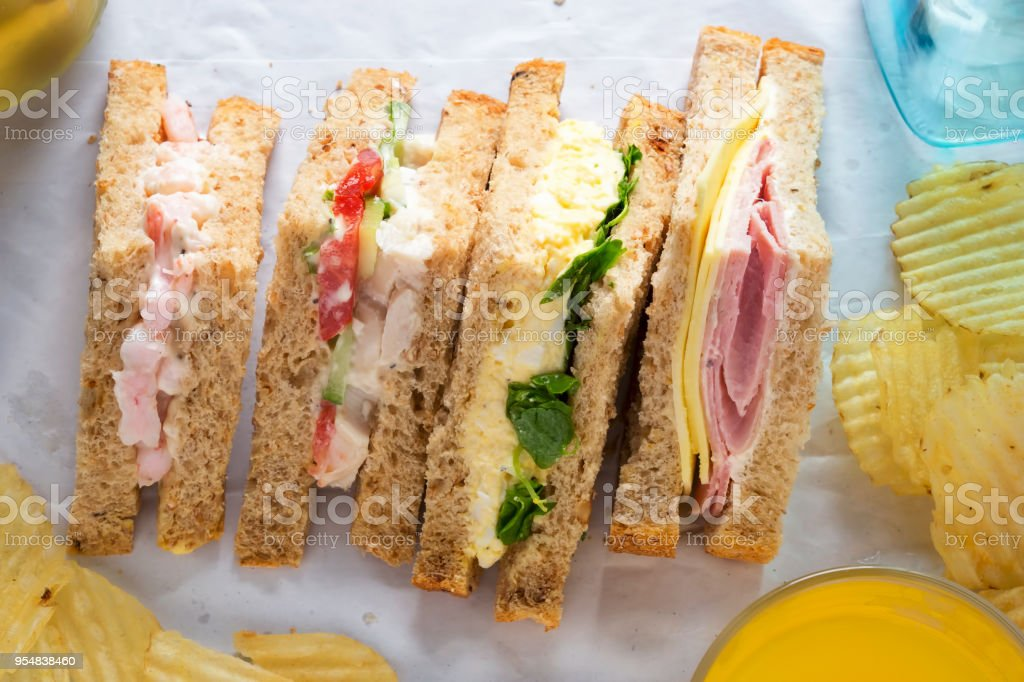 Selection of sandwiches on malted brown bread. Prawns with mayonnaise. Roast chicken breast, vine tomatoes, cucumber, mayonnaise. Egg mayonnaise  and watercress. Ham and cheddar cheese on mayo. stock photo