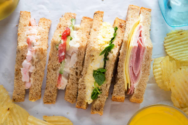 selection of sandwiches on malted brown bread. prawns with mayonnaise. roast chicken breast, vine tomatoes, cucumber, mayonnaise. egg mayonnaise  and watercress. ham and cheddar cheese on mayo. - sandwich stock pictures, royalty-free photos & images