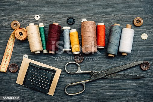 Equipment in the tailor shop, thread, sweing needle and scissors, buttons and fashion design plans. swing threads in row