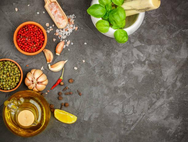 auswahl der gewürze und kräuter - knoblauch, salz, rosa, grün und schwarzem pfeffer, zitrone, basilikum, olivenöl. zutaten für das kochen. essen-hintergrund auf schwarzen tisch schiefer. draufsicht textfreiraum. - bärlauchsalz stock-fotos und bilder