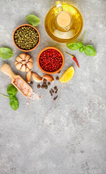 auswahl der gewürze und kräuter - knoblauch, salz, rosa, grün und schwarzem pfeffer, zitrone, basilikum, olivenöl. zutaten für das kochen. essen-hintergrund auf grau tisch schiefer. draufsicht textfreiraum - bärlauchsalz stock-fotos und bilder