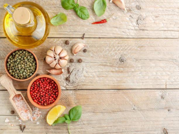 auswahl der gewürze und kräuter - knoblauch, salz, rosa, grün und schwarzem pfeffer, zitrone, basilikum, olivenöl. zutaten für das kochen. essen-hintergrund auf grau tisch. draufsicht textfreiraum - bärlauchsalz stock-fotos und bilder