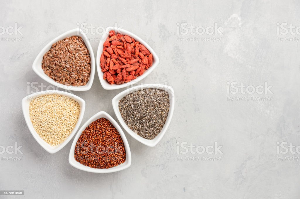 Selection of superfoods in white bowls on gray concrete background. Quinoa, chia seeds, goji berry and flax seeds. stock photo