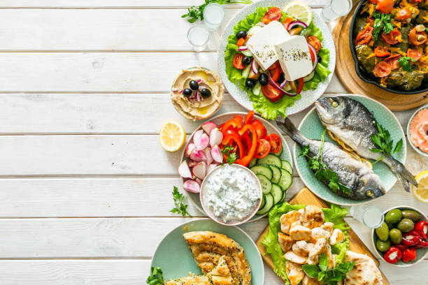 Selection of traditional greek food - salad, meze, pie, fish, tzatziki, dolma on wood background