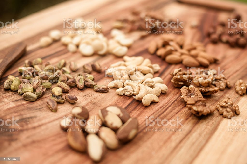 Selections of dried fruits or nuts on a wooden background stock photo