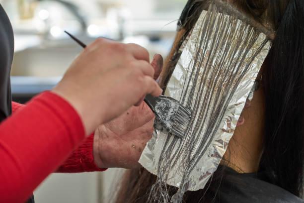 selektive bleichen und färben der haare - folien highlights stock-fotos und bilder
