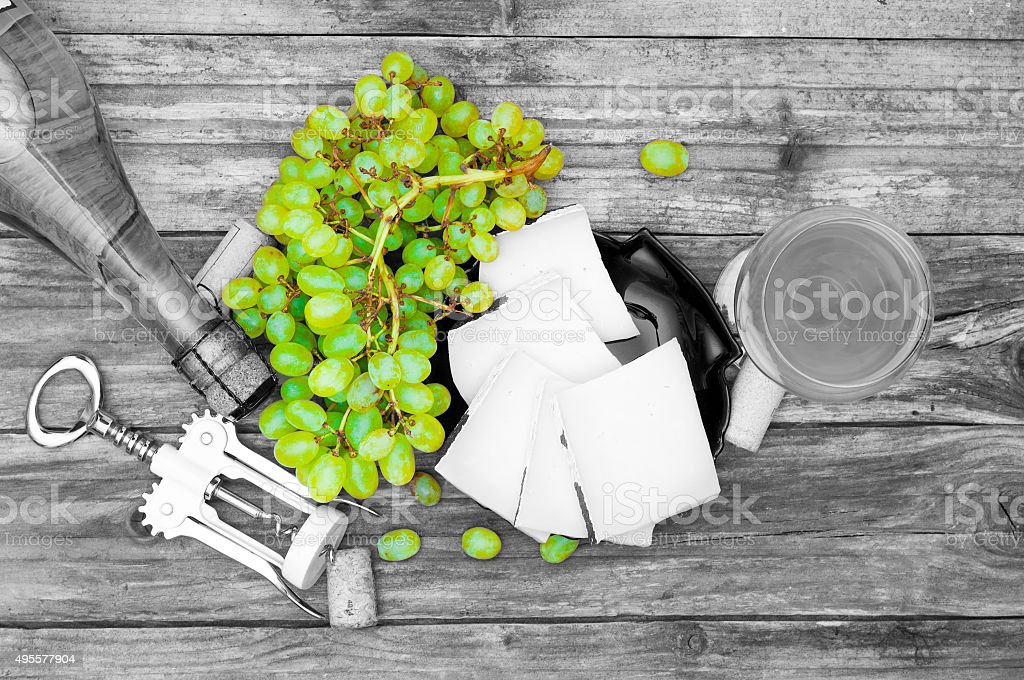 Selective desaturation of picture with cheese, grape and wine on stock photo