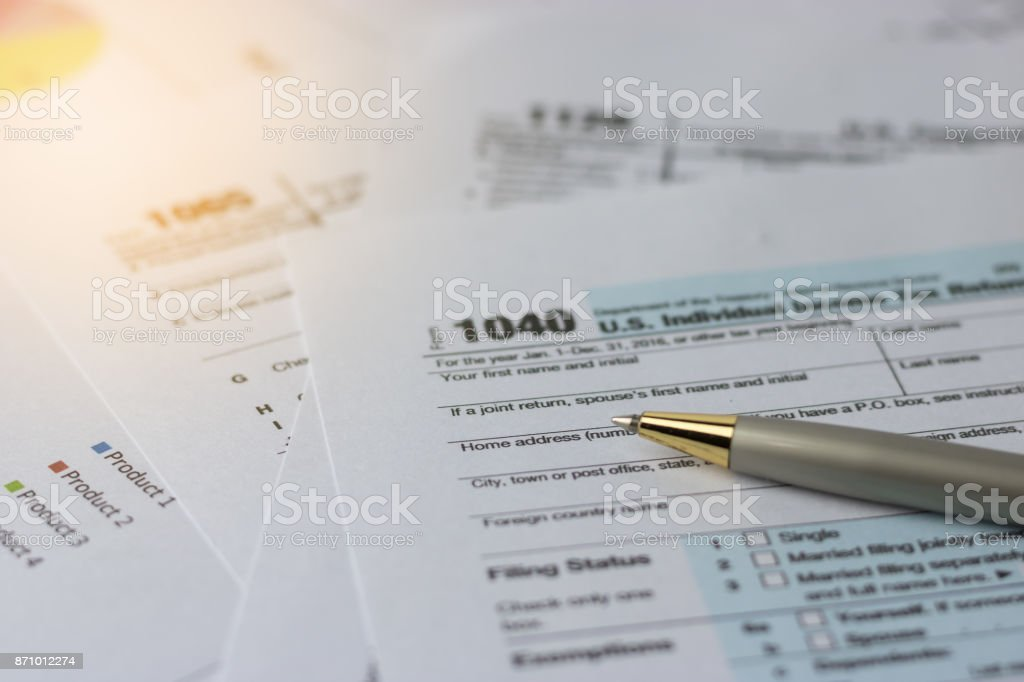 Selective focus a pen on US tax form 1040 on top for background / taxation concept stock photo
