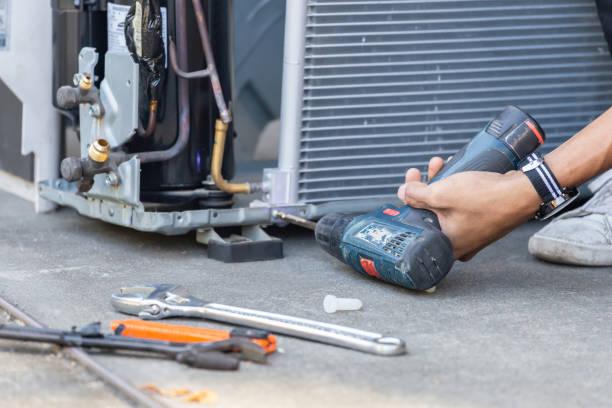 enfoque selectivo reparación del aire acondicionado, manos de hombre técnico utilizando un destornillador de fijación de moderno sistema de aire acondicionado - sólo hombres jóvenes fotografías e imágenes de stock