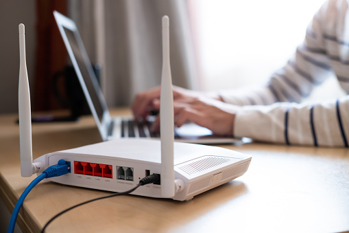 Selective focus at router. Internet router on working table with blurred man connect the cable at the background. Fast and high speed internet connection from fiber line with LAN cable connection.