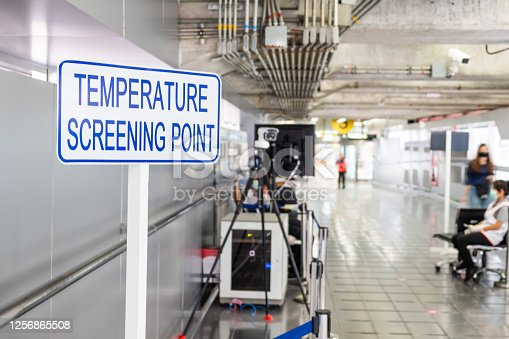 Selective focus at sign in front of the entrance of Airport terminal. Temperature screening point with thermal detection camera to scan and check body temperature to prevent Coronavirus.