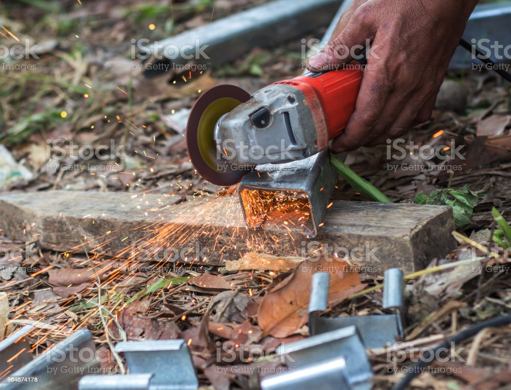 Selective focus at Steel cutter. Man use electric Steel cutter royalty-free stock photo