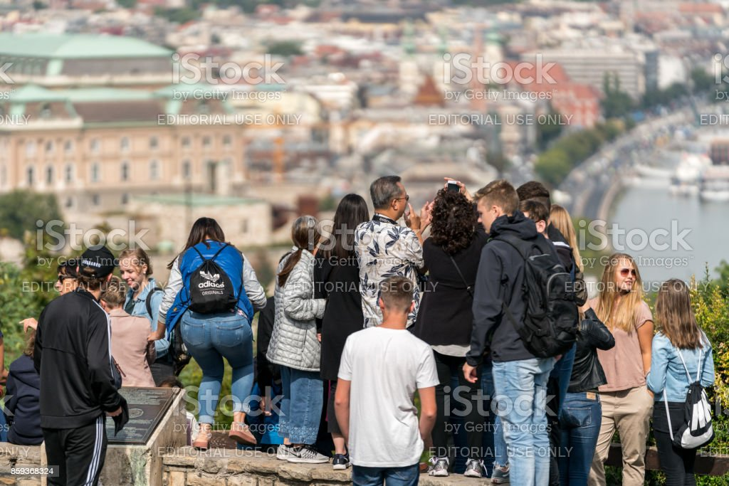Selective focus back view of a mixed group of young and old tourists standing at a viewpoint up high. royalty-free stock photo