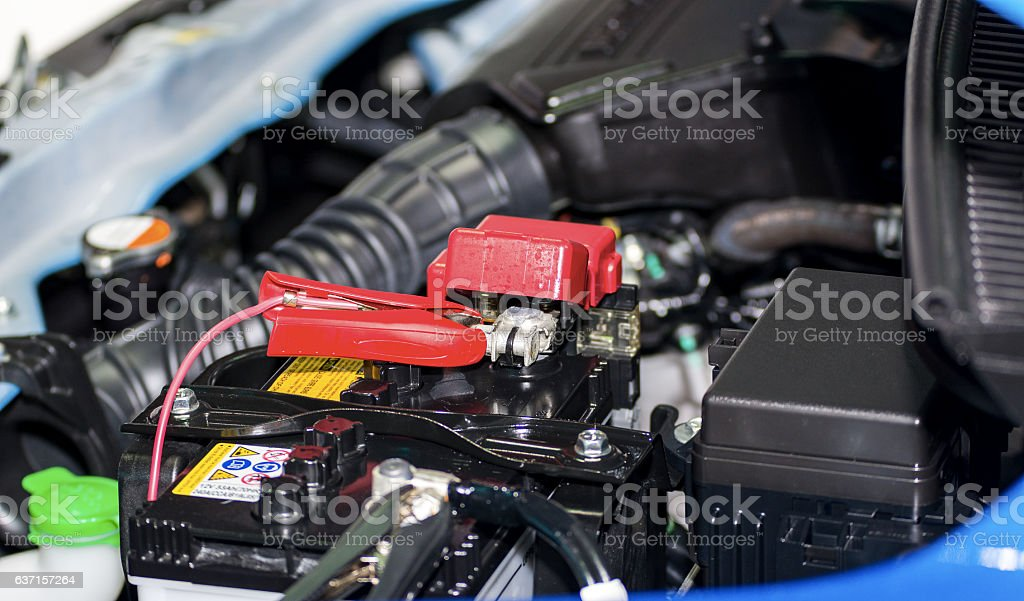 Selective focus charging car with electricity trough cables stock photo