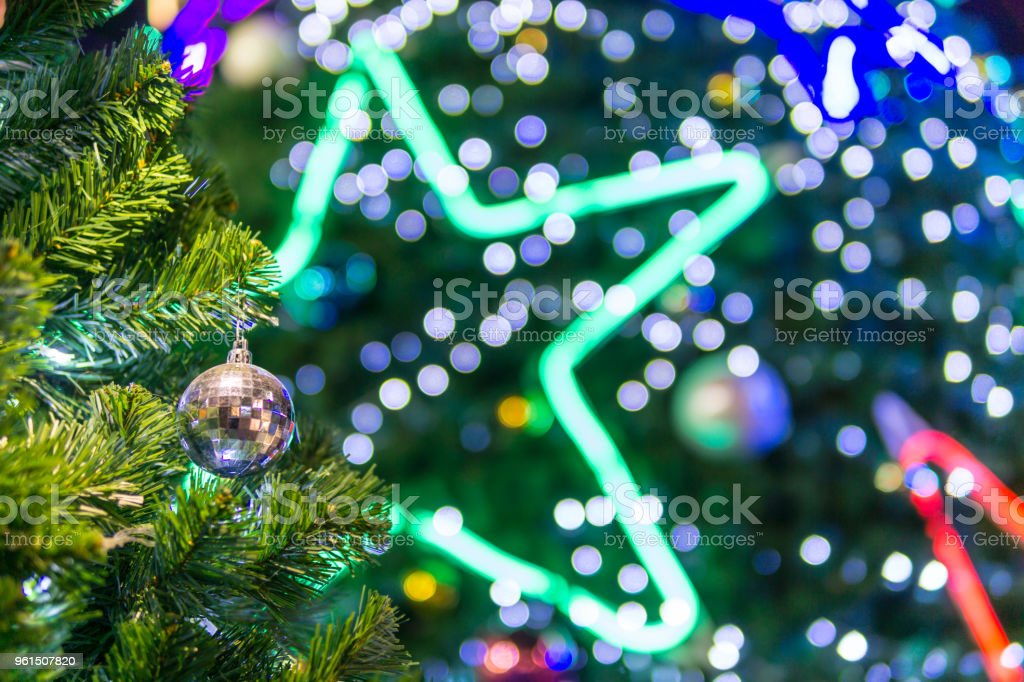 selective focus. close up of beautiful decorated christmas ball on the tree with blurred multi color bokeh background at night. copy space for text. xmas or new year concept. stock photo