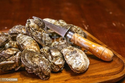 Selective focus closeup of a mess of Rappahannock River oysters on a wooden platter